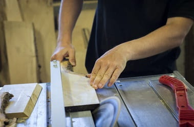 Man working with a circular saw in a workshop.